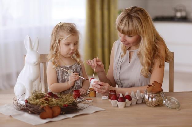 La madre e la figlia dipingono le uova di pasqua nella stanza alla tavola di festa. Foto Premium