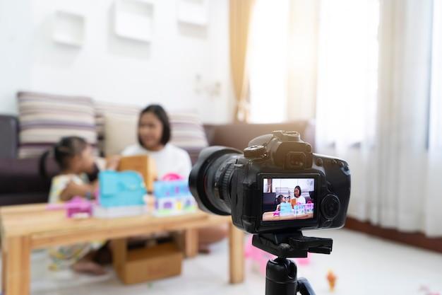 La madre e la figlia esaminano giocare ai giocattoli a casa. con la registrazione di video camera blogger Foto Premium