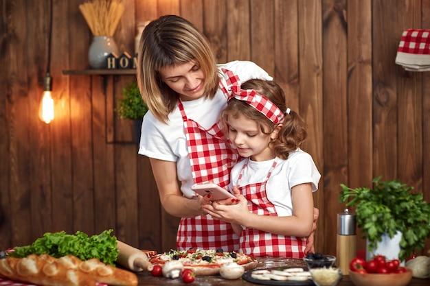 La madre e la figlia fotografano la pizza cotta sullo smartphone Foto Premium