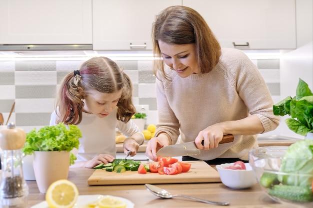 La madre e la figlia hanno tagliato le verdure a casa nella cucina Foto Premium