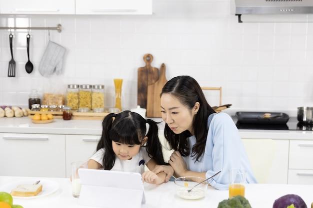 La madre e la figlia stanno mangiando la prima colazione e stanno guardando i media in una compressa Foto Premium