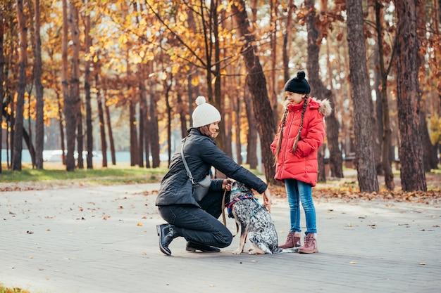 La madre felice e sua figlia che giocano con il cane in autunno parcheggiano Foto Gratuite