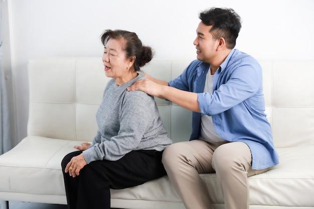 La madre senior asiatica della donna e il figlio del giovane in camicia blu massaggiano sua madre in salone Foto Premium
