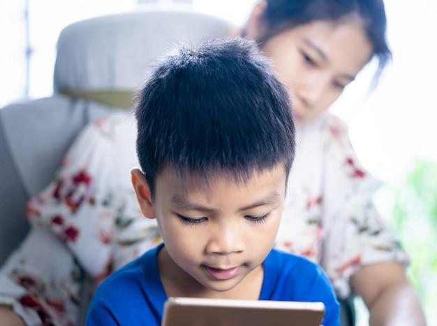 La madre sta guidando suo figlio a usare la tavoletta nel modo giusto Foto Premium