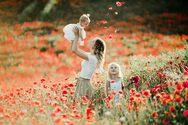 La madre tiene in braccio il suo bambino, la figlia maggiore sorride sul campo di papaveri Foto Gratuite