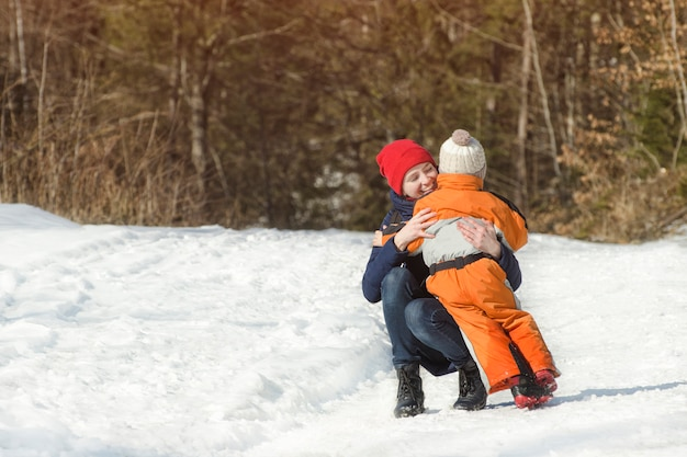 La mamma abbraccia il figlio piccolo su uno sfondo di pineta. giorno nevoso di inverno nella foresta di conifere Foto Premium