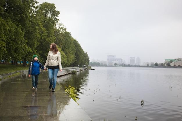 La mamma cammina con suo figlio in estate, cammina con la famiglia, le tradizioni familiari, l'amore e la comprensione Foto Premium