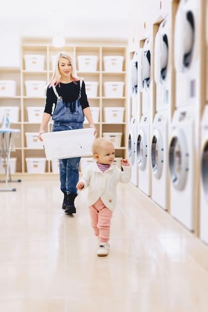 La mamma e il bambino in lavanderia prendono le cose e giocano Foto Premium