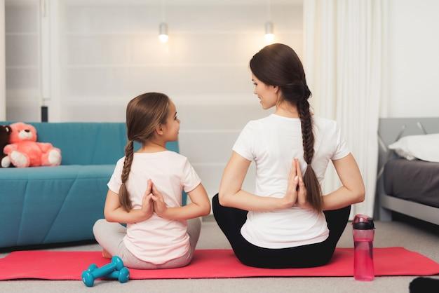 La mamma e la piccola figlia stanno facendo ginnastica sul tappeto Foto Premium