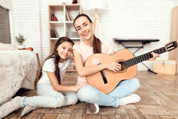 La mamma e sua figlia sono sedute sul pavimento con la chitarra. Foto Premium