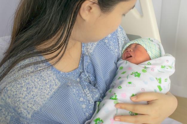 La mamma guarda il suo bambino appena nato a letto subito dopo il parto. foto di concetto di donna incinta, neonato, bambino, gravidanza. Foto Premium