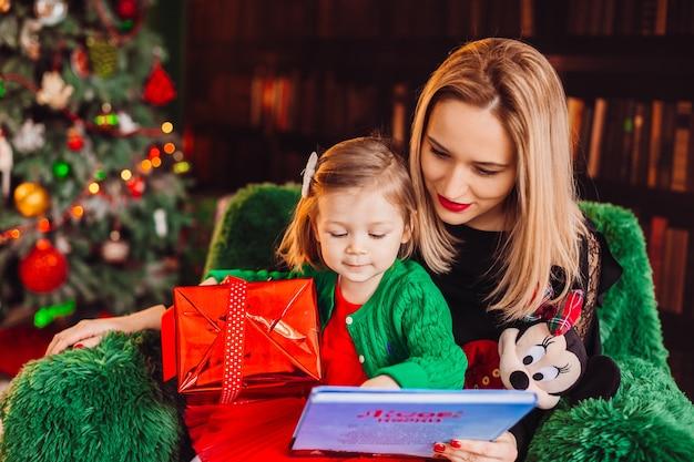 La mamma legge un libro con la sua piccola figlia seduta sulla sedia davanti all'albero di natale Foto Gratuite