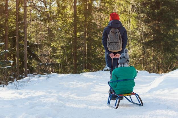 La mamma porta suo figlio su una slitta attraverso la foresta di conifere coperta di neve. Foto Premium