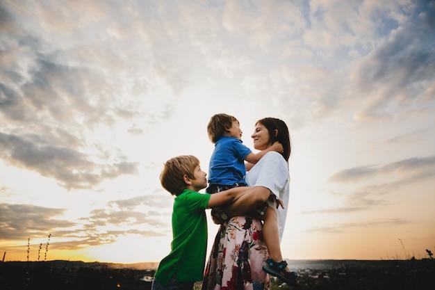 La mamma si abbraccia con i suoi due figlioletti teneri in piedi nei raggi Foto Gratuite