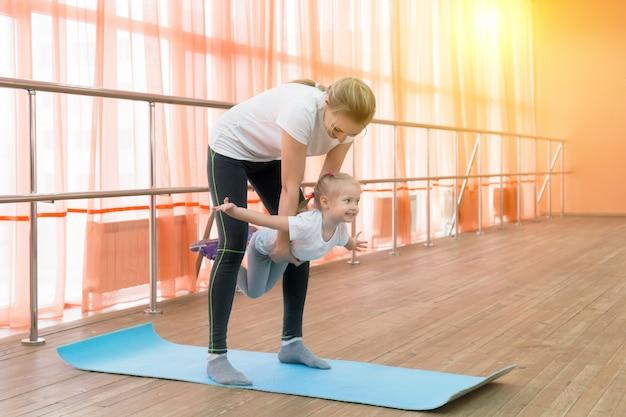 La mamma tiene in braccio una figlia che si esercita in ginnastica. Foto Premium