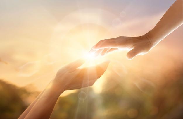 La mano amica di dio con la croce bianca su sfondo tramonto. Foto Premium