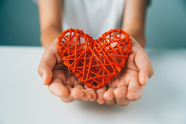 La mano dà cuore rosso per amore Foto Premium
