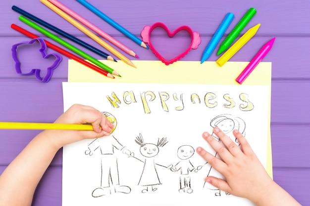 La mano del bambino dipinge lo schizzo della famiglia Foto Premium