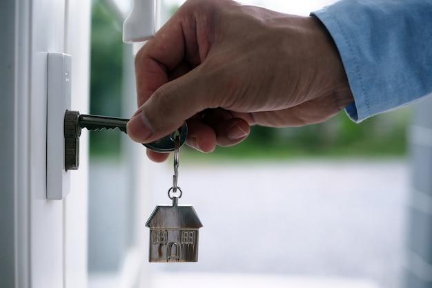 La mano del banchiere tiene la chiave di casa. concetto di mutuo casa e terra Foto Premium
