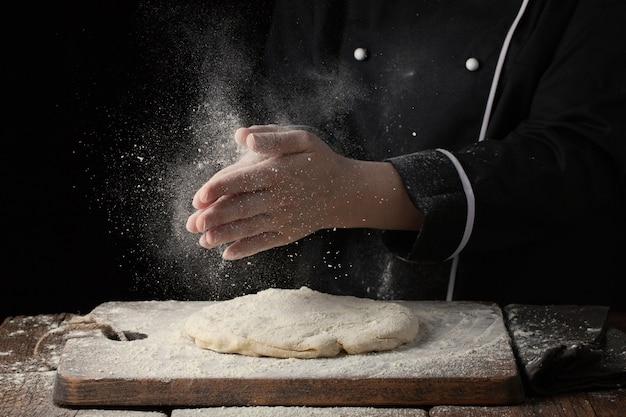 La mano del cuoco unico della donna applaude con spruzzata di farina bianca. Foto Premium