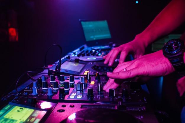 La mano del dj si mescola su un mixer professionale in una discoteca Foto Premium