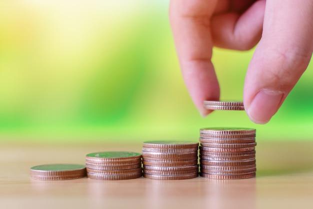 La mano del maschio che mette la moneta sulla pila dei soldi fa crescere i soldi di risparmio della crescita, investimento di affari di finanza di concetto Foto Premium