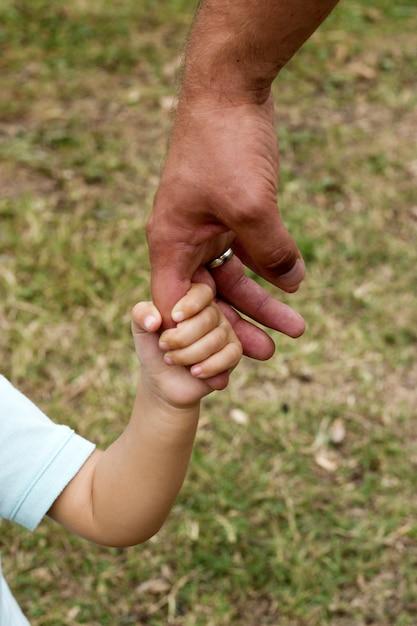 La mano del padre conduce suo figlio bambino nella natura estiva della foresta, fiducia nel concetto di famiglia Foto Premium