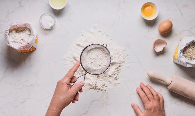 La mano del panettiere setaccia la farina al setaccio sul bancone della cucina Foto Gratuite
