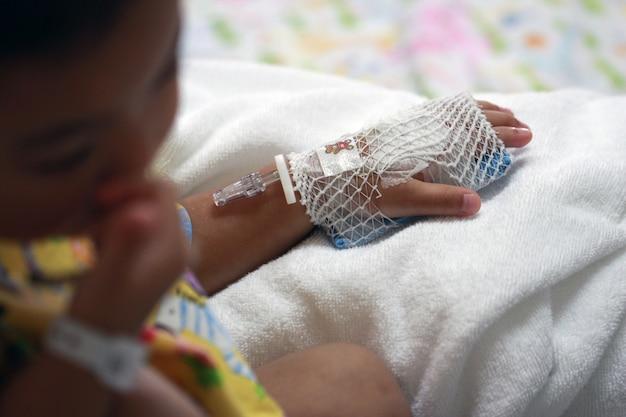 La mano del paziente dei bambini si prepara per la soluzione salina endovenosa nell'ospitale. Foto Premium