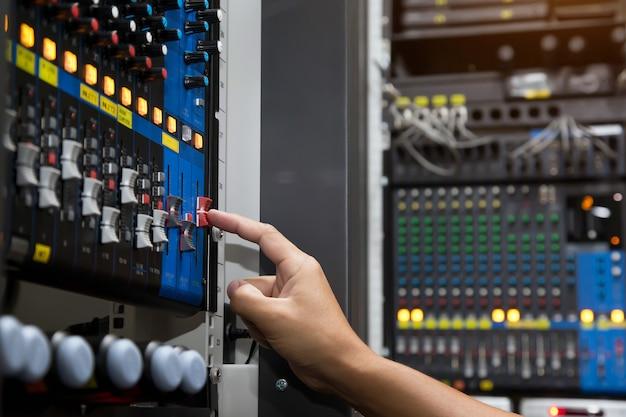 La mano del primo piano regola il volume sul mixer audio Foto Premium