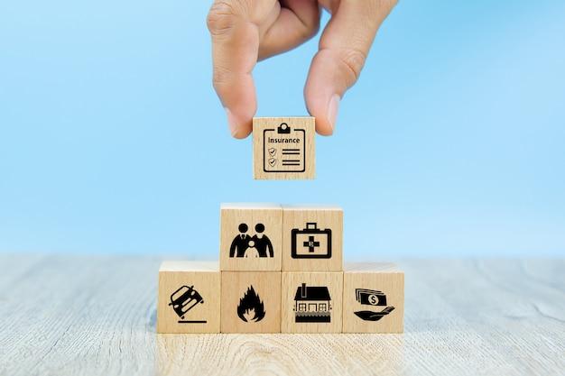 La mano del primo piano sceglie i blocchi di legno rossi di un giocattolo con l'icona di assicurazione per l'assicurazione della famiglia di sicurezza Foto Premium