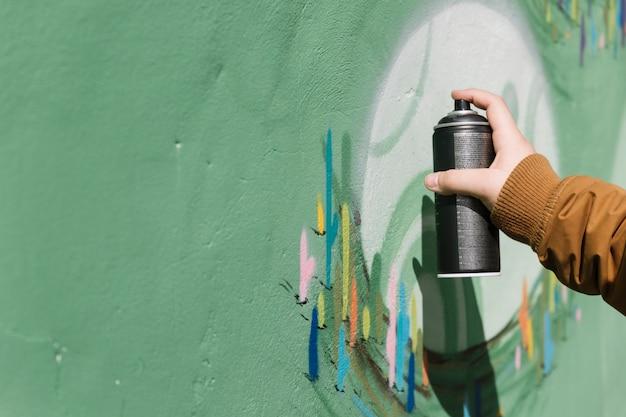 La mano dell'artista che spruzza sulla parete dei graffiti con lo spruzzo dell'aerosol Foto Gratuite