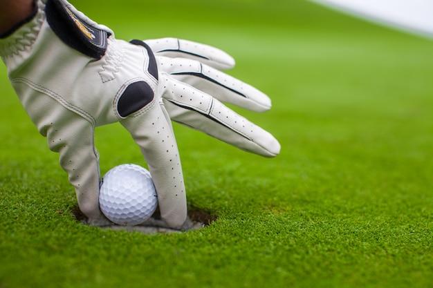 La mano dell'uomo che mette una pallina da golf nel foro sul campo verde Foto Premium