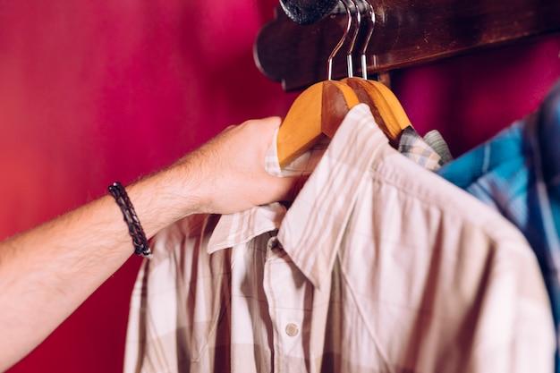 La mano dell'uomo che prende la camicia del gancio del cappotto dal gancio della cremagliera sulla parete rossa Foto Gratuite