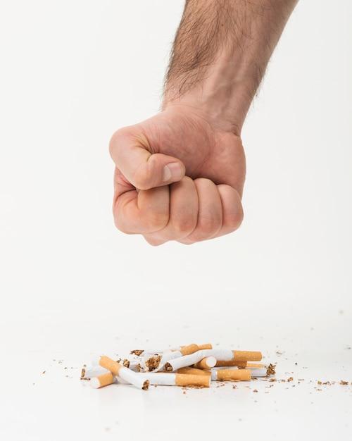 La mano dell'uomo che prova a schiacciare le sigarette sul contesto bianco Foto Gratuite