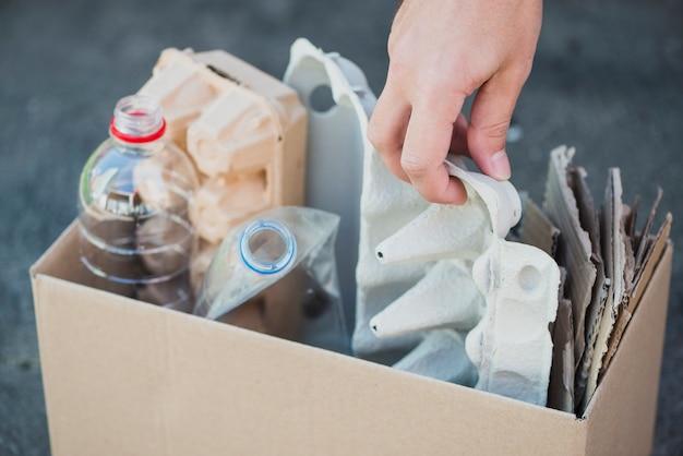 La mano dell'uomo che raccoglie le bottiglie di plastica e il cartone delle uova nella scatola di riciclo Foto Gratuite
