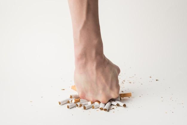 La mano dell'uomo che rompe le sigarette con il suo pugno sulla superficie bianca Foto Gratuite