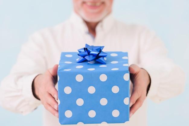La mano dell'uomo che tiene il contenitore di regalo di compleanno avvolto blu Foto Gratuite
