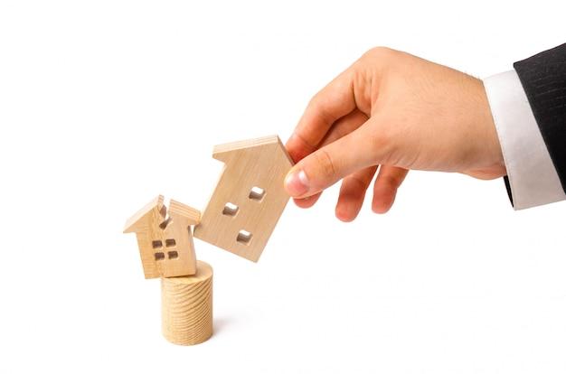 La mano dell'uomo d'affari sostituisce la vecchia casa con una danneggiata per una nuova. Foto Premium