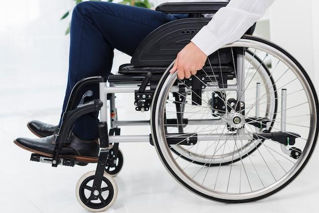 La mano dell'uomo d'affari sulla ruota che si siede sulla sedia a rotelle Foto Gratuite