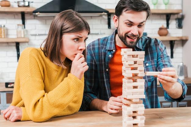 La mano dell'uomo prende o mette un blocco a una torre instabile e incompleta di blocchi di legno Foto Gratuite