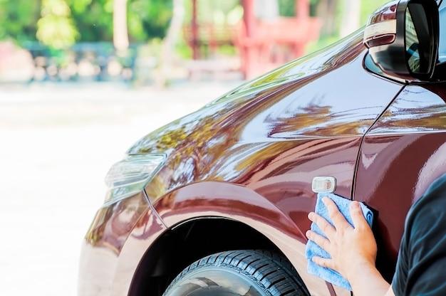 La mano dell'uomo sta pulendo e cerando la macchina Foto Gratuite