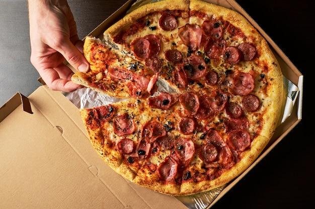 La mano dell'uomo sta tenendo la fetta di pizza al formaggio da tutta la pizza in fondo scuro tavolo di scatola di cartone Foto Premium