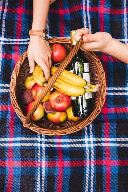 La mano della coppia sul cestino da picnic con frutta e bottiglia di champagne Foto Gratuite