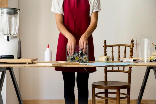 La mano della donna che mescola i documenti lacerati in acqua Foto Gratuite