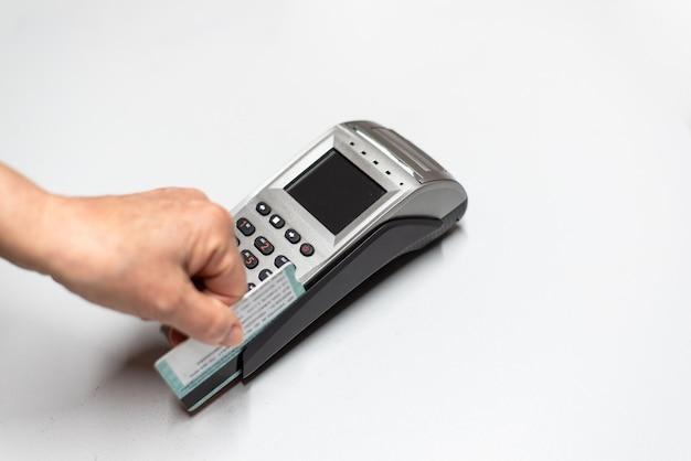 La mano della donna che passa la carta di credito da un dataphone, lettore di schede per caricare in tempo di vendite. Foto Premium
