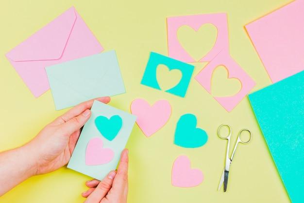 La mano della donna che prepara la cartolina d'auguri di forma del cuore su fondo giallo Foto Gratuite