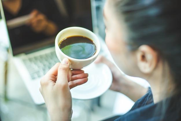 La mano della donna che tiene una tazza di caffè caldo sulla scrivania Foto Premium
