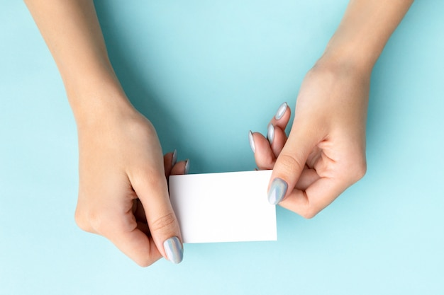 La mano della donna con il biglietto da visita alla moda della tenuta del manicure Foto Premium