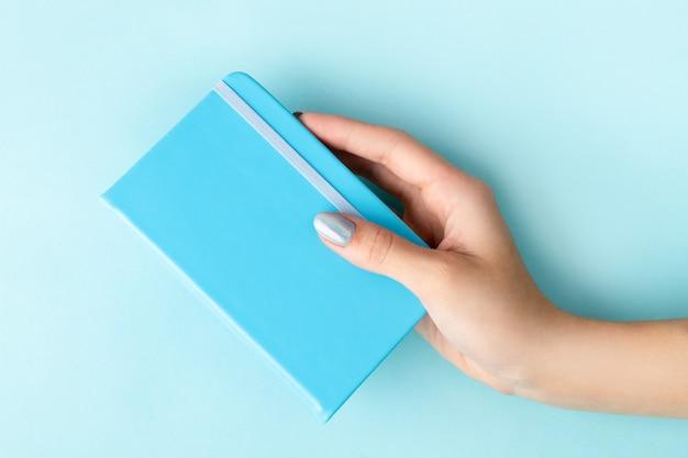 La mano della donna con il blocco note della tenuta del manicure su fondo blu Foto Premium